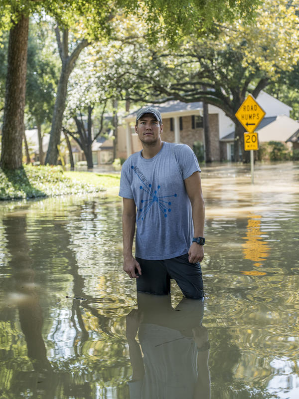 Jared McCurley walks through the flooded streets near his home in the Nottingham Forrest subdivision.