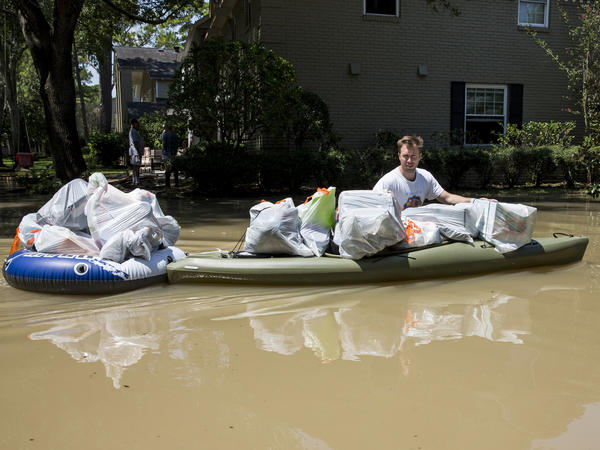 A resident tries to save some of his belongings from the flooded Buffalo Bayou in Houston.