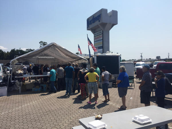 People line up for a hot lunch of jambalaya and pulled pork in the Market Basket parking lot which has become a response hub for storm victims in Orange, Texas.