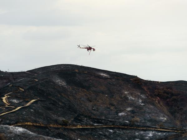 A firefighting helicopter flies over burned hills during the La Tuna fire in Los Angeles, California on Sunday.