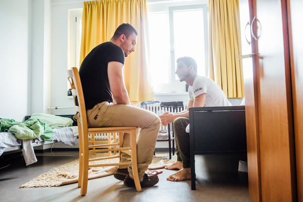 Ahmad Chahabi (left) chats with a newly arrived refugee in the shelter where he himself used to live in the south of Berlin. Chahabi is now a peer counselor.