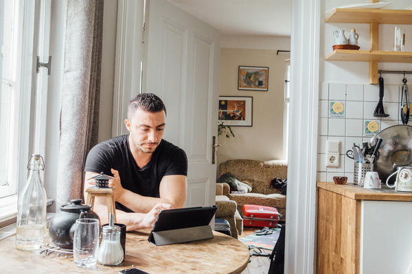 Chahabi, photographed in his kitchen, uses this tablet for remote counseling sessions with refugees.
