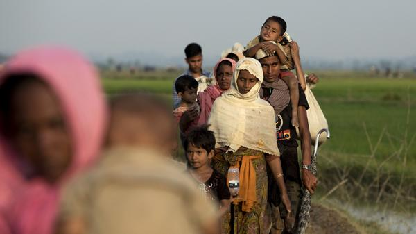 Rohingya refugees from Myanmar's Rakhine state walk the border with Bangladesh on Monday.