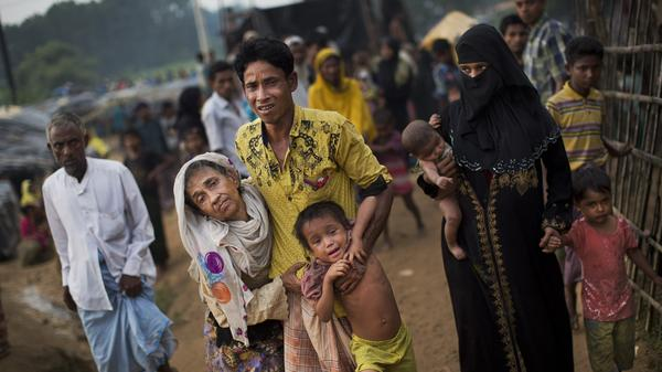 A Rohingya Muslim helps his elderly family member and child as they arrive at a refugee camp on the Bangladesh side of the border Tuesday. The man said he lost several family members in Myanmar.