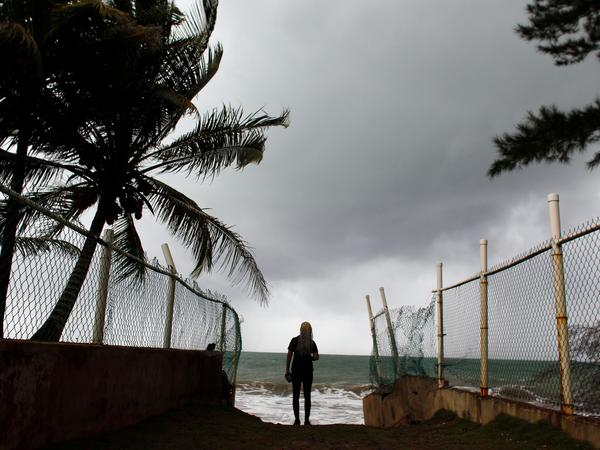 A woman looks at heavy surf as Hurricane Irma approaches Puerto Rico in Luquillo on Wednesday.