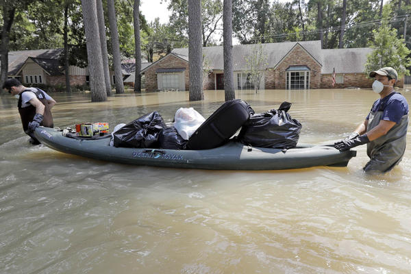 Gaston Kirby, left, is helped by friend Juan Minutella after gathering the last of his belongings from his flooded home in the aftermath of Hurricane Harvey Monday, Sept. 4, 2017 in Houston. (David J. Phillip/AP)