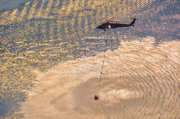 An Air National Guard Blackhawk helicopter scoops water during a 2015 wildfire activation.