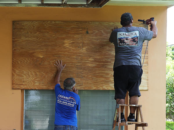 Men put up shutters to prepare a house for Hurricane Irma on Wednesday in Miami.