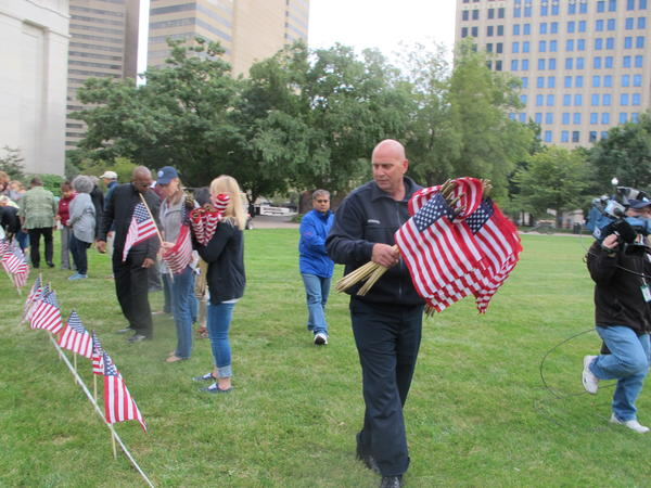 Volunteers helped hand out flags to others to place on the West Lawn.
