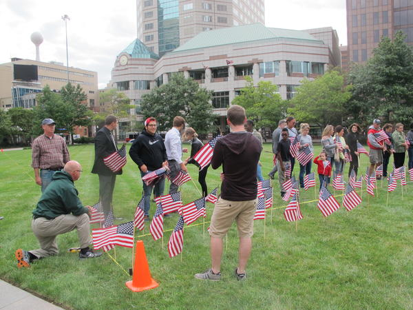 Volunteers line up to place flags on the Statehouse lawn.
