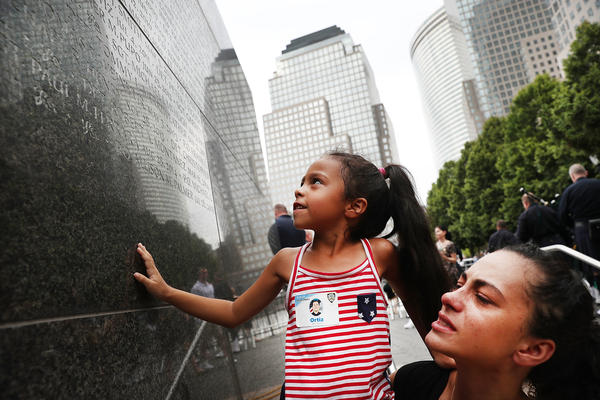 Bernadette Ortiz holds her daughter, Adriana, last year as she looks for the name of her grandfather, New York City Police Officer Edwin Ortiz, at a wall commemorating fallen officers in New York City. Families gathered at the wall following a procession in Lower Manhattan to mark the anniversary of the Sept. 11 attacks and honor officers who were killed.