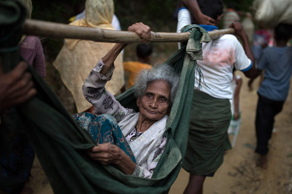 Rohingya Muslim refugees carry an elderly woman to a settlement, after crossing the Myanmar Bangladesh border on September 07, 2017 in Balukhali Bazar, Bangladesh. Thousands of Rohingya continue to cross the border after violence erupted in Myanmar's Rakhine state when the country's security forces allegedly launched an operation against the Rohingya Muslim community.