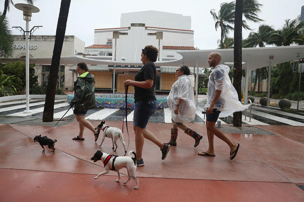 People walk along Lincoln Road Mall as Hurricane Irma approaches in Miami Beach, Fla., on Saturday.