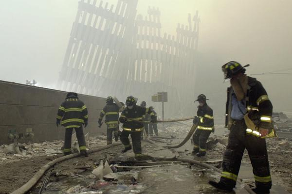 Firefighters work beneath the vertical struts of the World Trade Center's twin towers, in Lower Manhattan, following the attacks of Sept. 11, 2001.