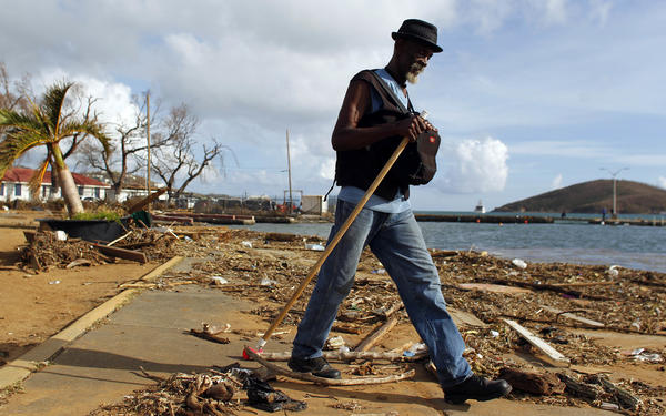 A man walks past debris Sunday on St. Thomas, in the U.S. Virgin Islands. Days after Hurricane Irma smashed through the U.S. territory on its way to Florida, residents say they barely recognize their homes.