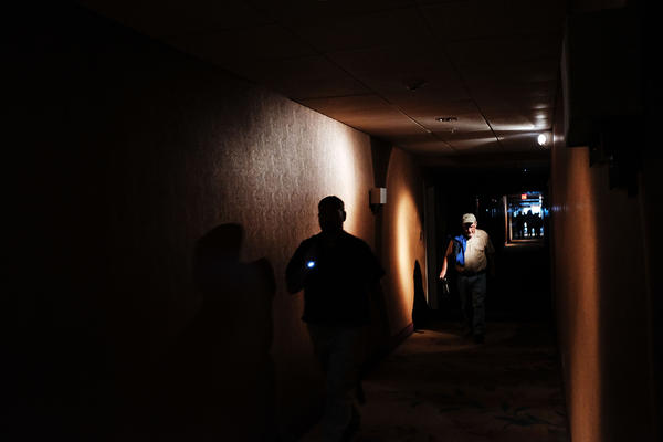 Hotel guests walk through dark hallways after the electricity was cut at a hotel on Saturday in Fort Myers, Fla.