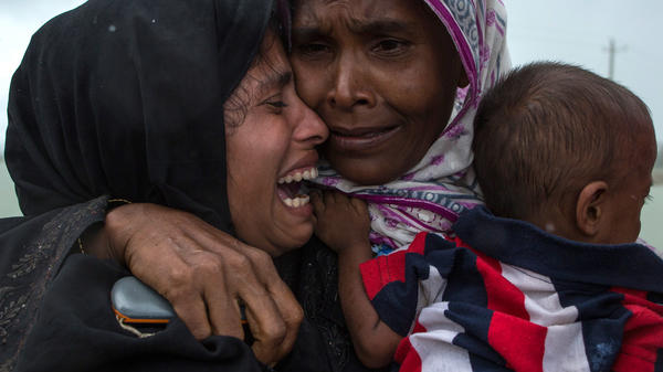 Rohingya refugees embrace one another, finally reunited after a perilous journey by boat from Myanmar to Bangladesh.
