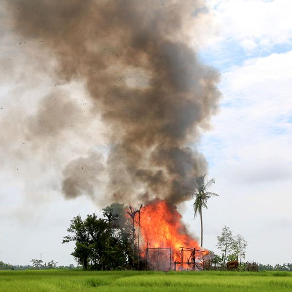A house in Rakhine state is consumed by flames Thursday, as journalists look on. The reporters were taken on a government-sponsored tour for media through the region.