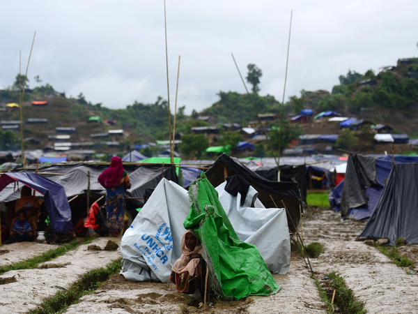 A Rohingya woman sits next to a newly built shelter in a makeshift Bangladeshi camp on Saturday.