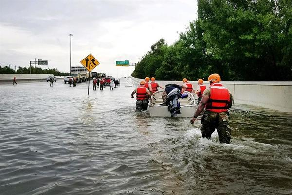 National Guard members wade through a flooded highway in the aftermath of Hurricane Harvey.