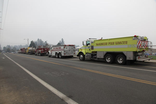 <p>Water tankers and other firefighting trucks line up outside the high school in Brookings.</p>