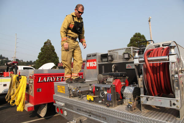 <p>A firefighter makes sure his equipment is in good working order on Aug. 25, 2017 after a long day on the lines fighting the Chetco Bar wildfire near Brookings, Oregon.</p>