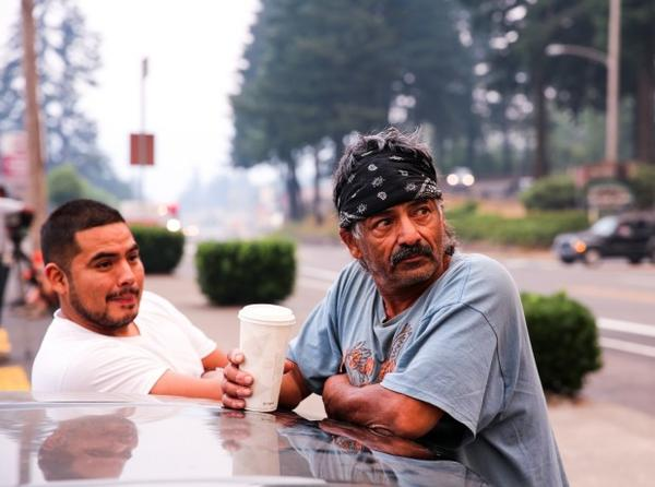 <p>Rudy, right, who sells fish at the farmer's market in Cascade Locks, said Labor Day is normally the busiest day of the year for his business. But with the Eagle Creek Fire threatening the town, the market sat mostly empty Monday, Sept. 4, 2017.</p>