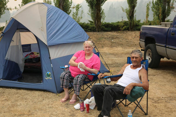 """<p>Larry and Tammy South live in a trailer court in Cascade Locks that was evacuated. The town has been home for the last 36 years. Tammy holds a rag over her mouth to block out the thick smoke. """"I'm still scared,"""" South said. </p>"""