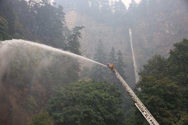 <p>A hot shot sprays water on the area surrounding Multnomah Falls.</p>