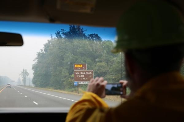 <p>A press convoy moves along Highway 84 toward Multnomah Falls with fire officials.</p>