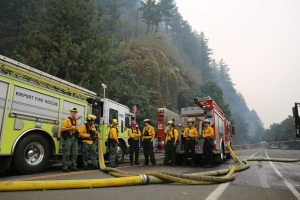 <p>Fire crews from different parts of the state rest at the bottom of Multnomah Falls where they worked to prevent the Multnomah Falls Lodge from burning on Sept. 6, 2017.</p>