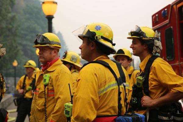 <p>Fire crews take a break at the foot of Multnomah Falls Sept. 6, 2017. The Eagle Creek fire threatened the Multnomah Falls Lodge, but the power was still working. </p>