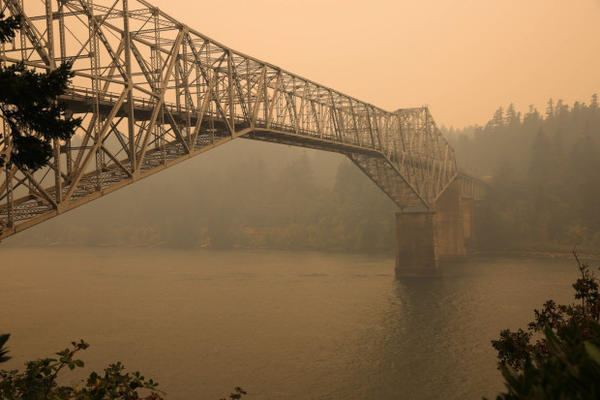 <p>Smoke blocks the view of the Columbia River Gorge behind Bridge of the Gods in Cascade Locks.</p>