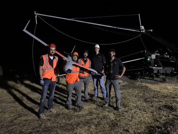 "Insitu unmanned aircraft operators pose with the ScanEagle drone after disconnecting it from the ""SkyHook"" retrieval system behind them."