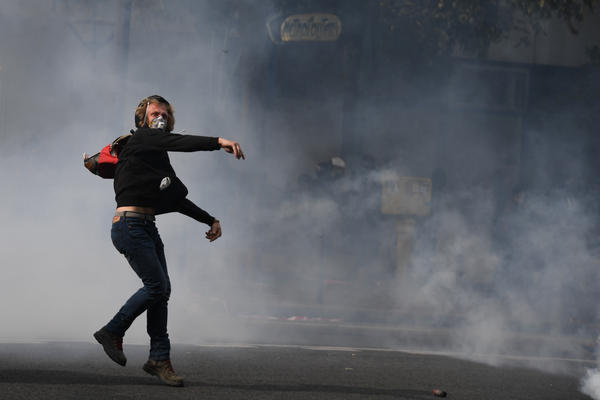 A demonstrator throws a projectile during a protest Tuesday called by several French unions in Paris.