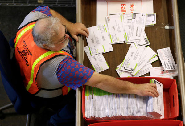<p>Election worker Harry Nein processes ballots at Multnomah County election headquarters in Portland, Ore., Tuesday, Nov. 8 2016.</p>