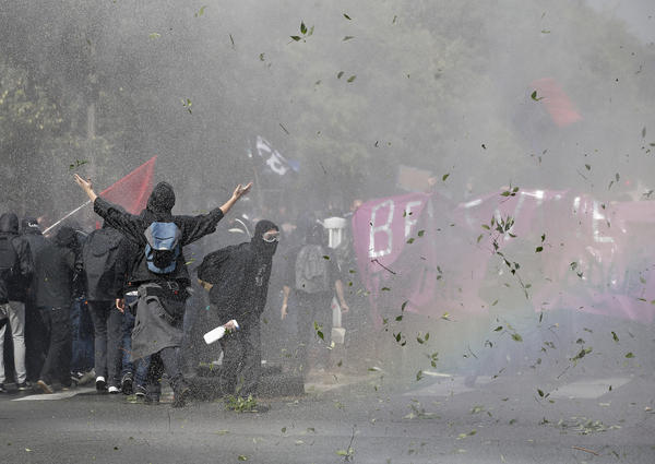 Demonstrators take cover in Paris after clashing with police during a protest march against President Emmanuel Macron's new labor policies.
