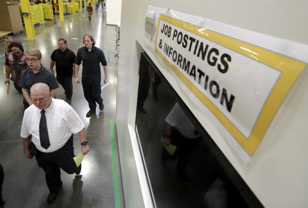 Job candidates take a tour of the Amazon fulfillment center in Robbinsville, N.J., during a job fair last month. The Census Bureau says increased employment is what's driving higher income numbers.