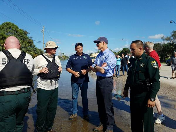 Governor Rick Scott meets with Bonita Mayor Peter Simmons and law enforcement in a flooded portion of Bonita Springs.