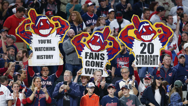 Fans of the Cleveland Indians celebrate a 2-0 victory over the Detroit Tigers Tuesday night in Cleveland. The Indians won their 20th game in a row, tying the American League record.