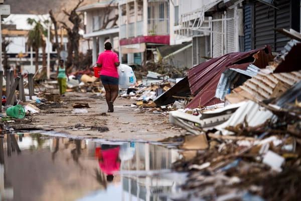A woman walks on a street in Marigot on September 11, 2017 on the French Caribbean island of Saint Martin after it was hit by Hurricane Irma.