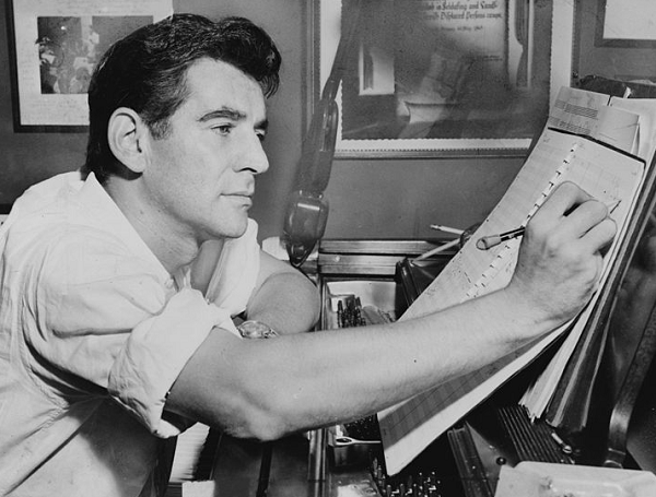 Leonard Bernstein seated at piano, making annotations to musical score