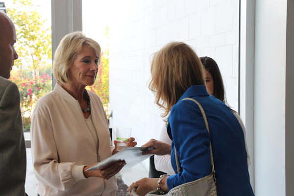 State Rep. Cindy Holscher, right, an Olathe Democrat, hands U.S. Secretary of Education Betsy DeVos a packet of statements from groups like Stand Up Blue Valley that oppose her position on school choice.