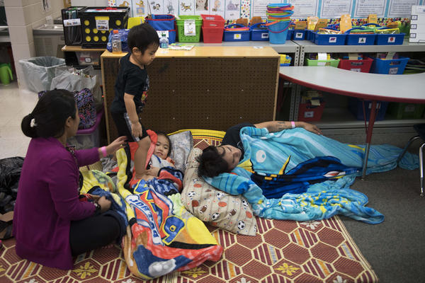 A young boy steps on his sister as he moves around the tight confines of a classroom-turned-shelter at Pizzo Elementary School in Tampa, Fla.
