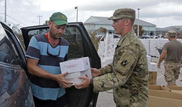 A member of the National Guard hands over boxes of food to Patrick Garvey in the aftermath of Hurricane Irma, Thursday, Sept. 14, 2017, in Big Pine Key.
