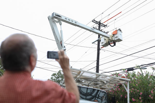 Mark Hastings watches as an Austin Energy crew restores power to his office building near North Lamar and 12th Street on Aug. 26. A tree fell through electrical wires during Tropical Storm Harvey.