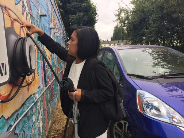 <p>Ana Mendoza unplugs a Honda Fit EV at a low-income apartment complex in Northeast Portland's Cully neighborhood. It's one of three vehicles in a new car-sharing program organized by Hacienda Community Development Corporation and the electric car advocacy group Forth.</p>