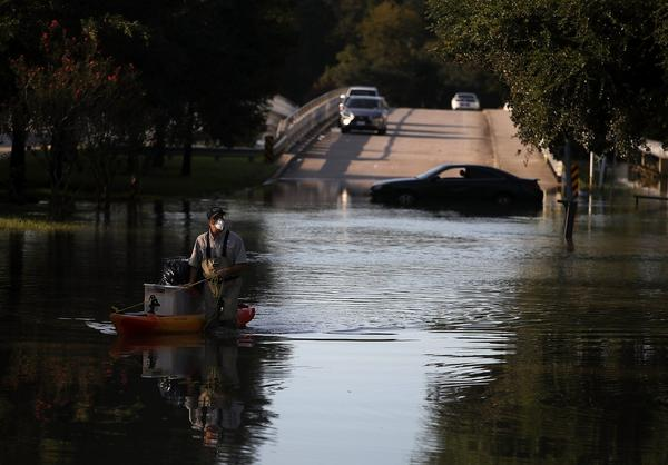 A resident pulls personal belongings on a kayak as he wades through floodwaters on Sept. 6, 2017 in Houston, Texas. (Justin Sullivan/Getty Images)