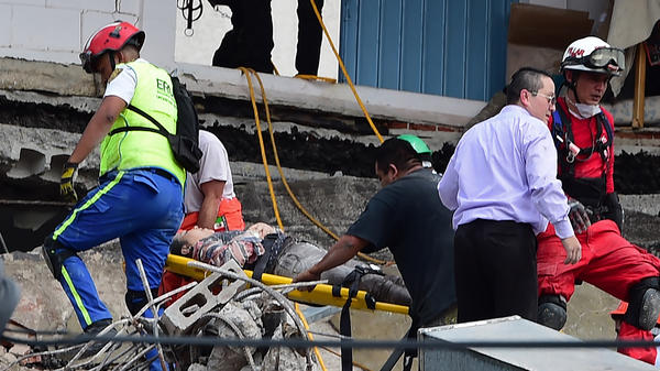 A woman is carried on a stretcher after being pulled from the debris of a collapsed building in Mexico City on Tuesday.