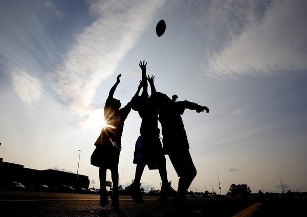 Kids play football in the parking lot before an NFL preseason football game between the New England Patriots and the New York Giants, Thursday, Aug. 31, 2017, in Foxborough, Mass. (Winslow Townson/AP)